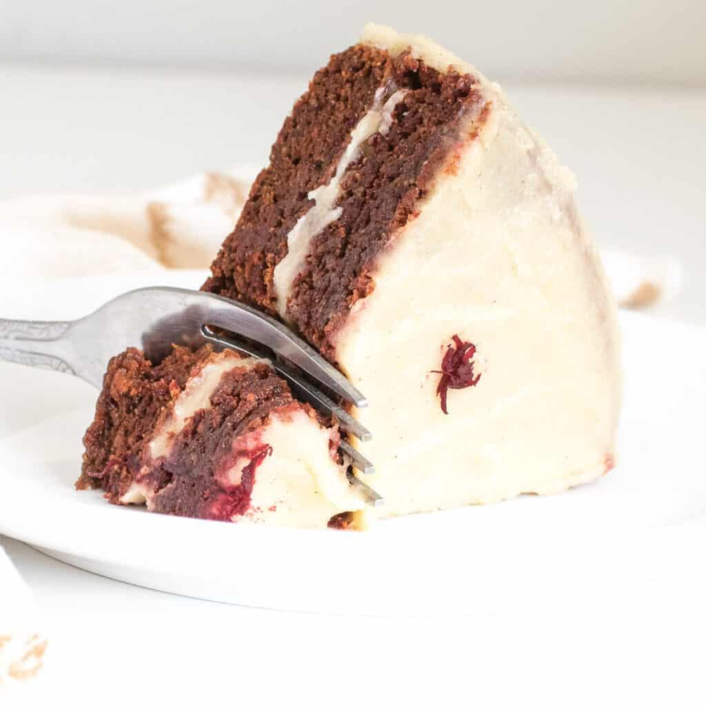 a fork digging into a slice of vegan red velvet cake.