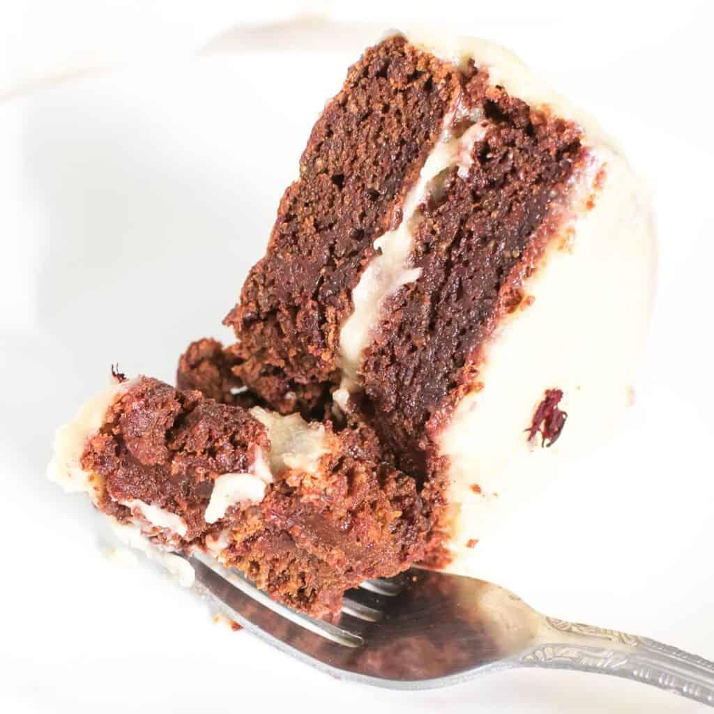 a fork picking a bite of the sliced vegan red velvet cake.