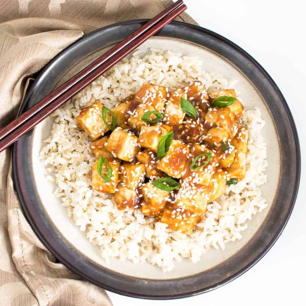 top view of sesame tofu over the bed of brown rice.