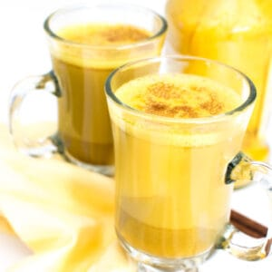 a 45 degree angle view of turmeric latte in serving glasses.