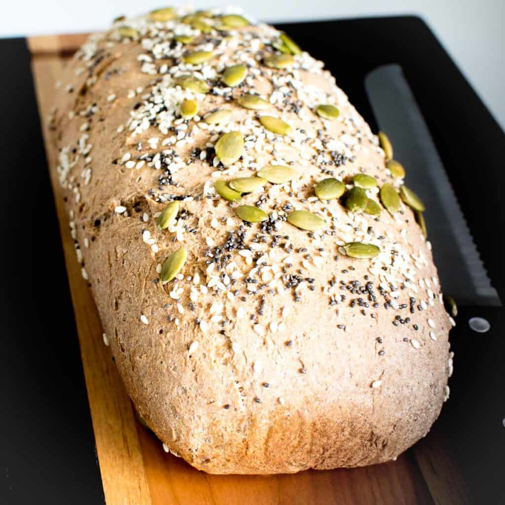 fresh baked whole wheat bread on a cutting board cooling down.