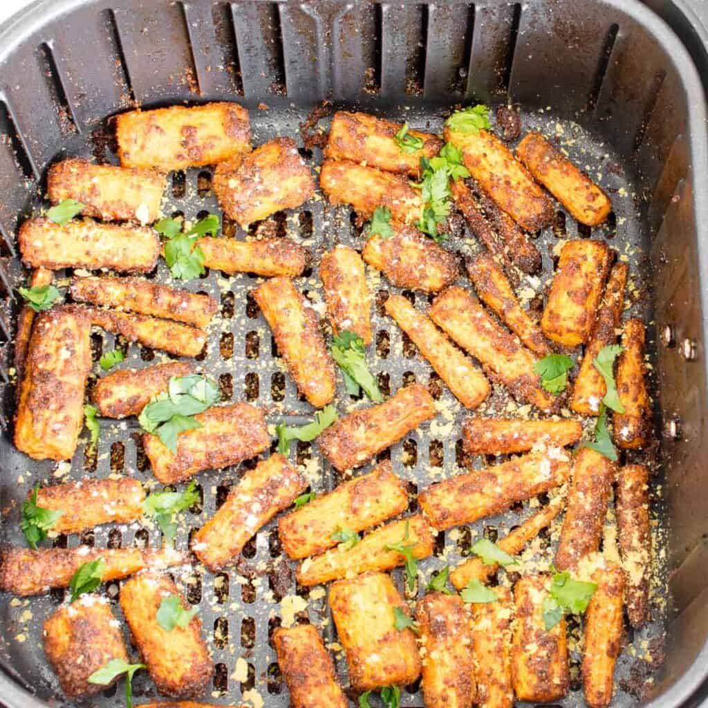 top view of air fryer carrots with the garnishes in the basket.