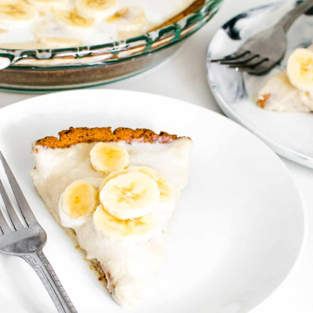 a 45 degree angle view of the vegan banana cream pie in a serving plate along with the whole pie at the backdrop.