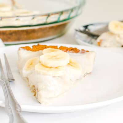 a front view of vegan banana cream pie slice in the serving plate along with the whole table spread.