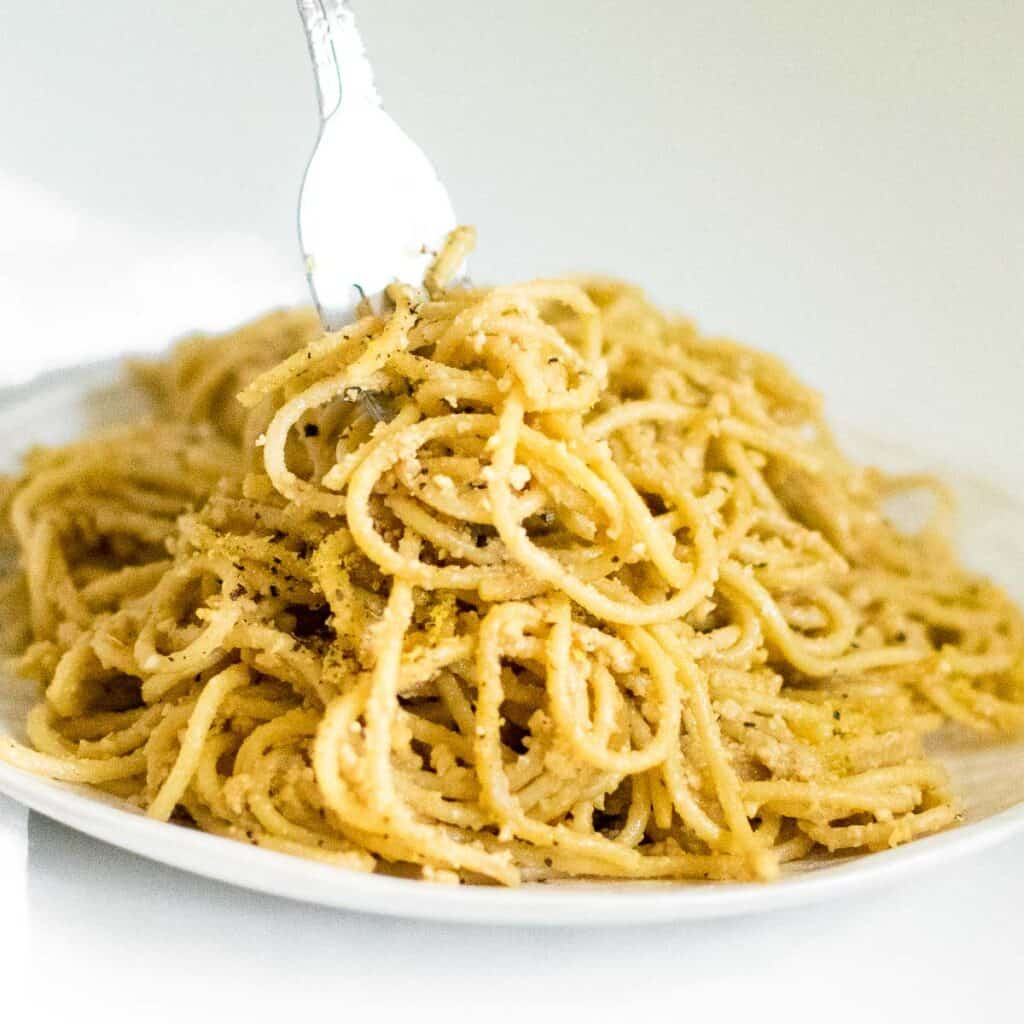 a fork picking up vegan cacio e pepe from the serving plate.