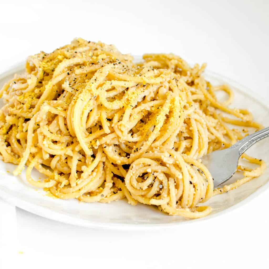 a side view of a fork rolled in vegan cacio e pepe.
