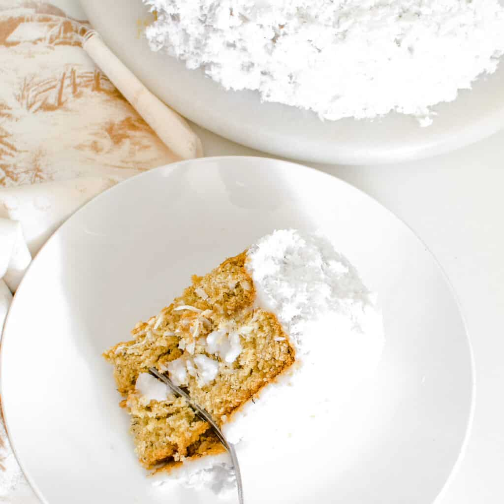 top view of a fork digging through a slice of vegan coconut cake.