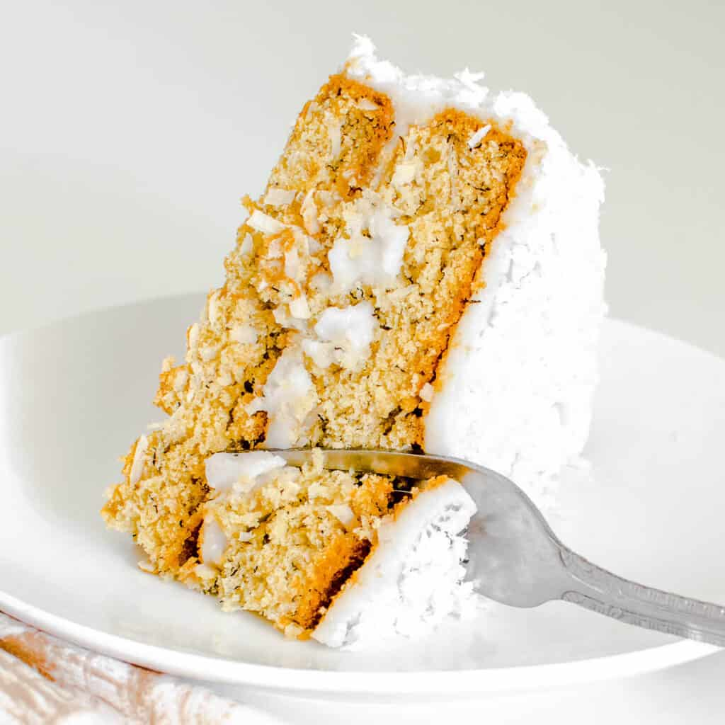 a fork digging through a slice of vegan coconut cake cake.
