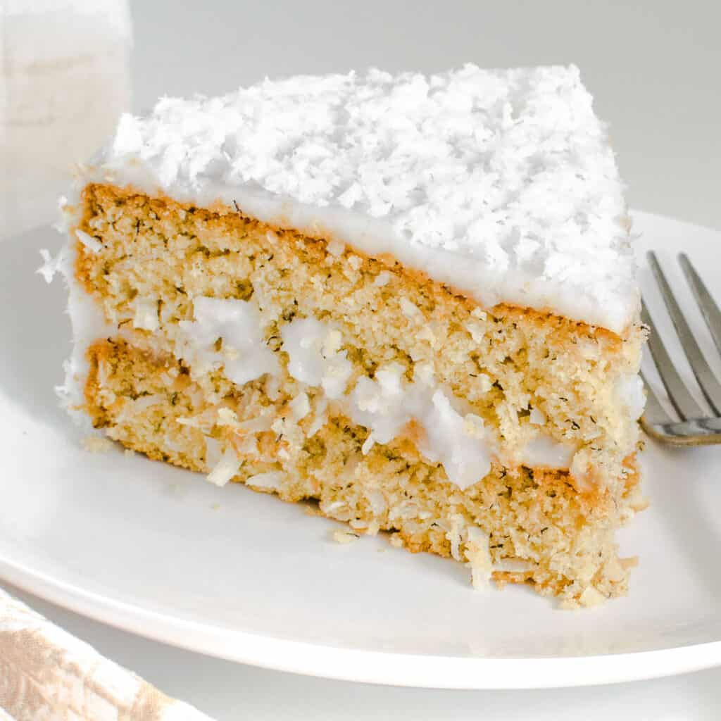 a close view of a slice of vegan coconut cake on a serving plate.