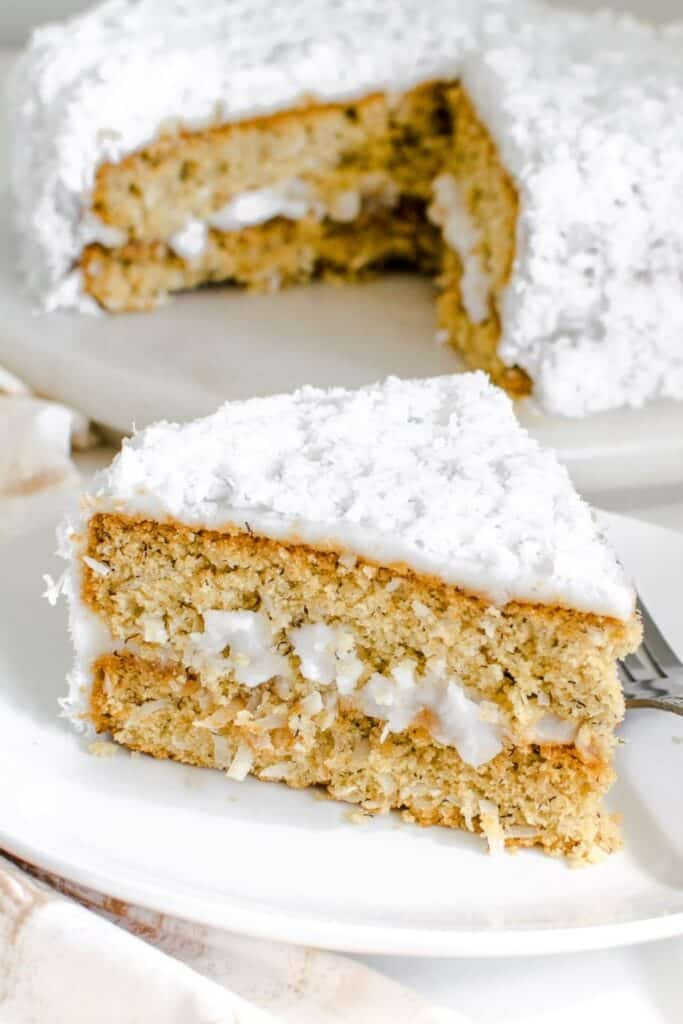a slice of vegan coconut cake on a serving plate with the entire cake at the backdrop.