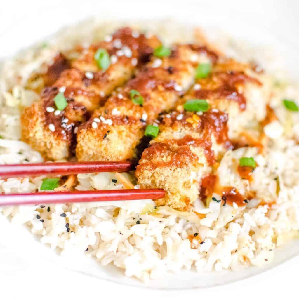 chopsticks trying to pick tofu katsu.