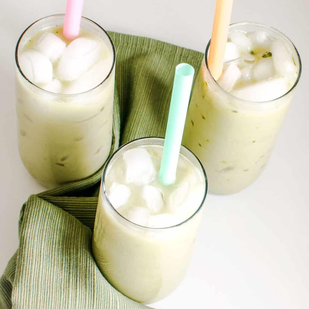 top view of serving glasses filled with iced matcha latte along with straws.