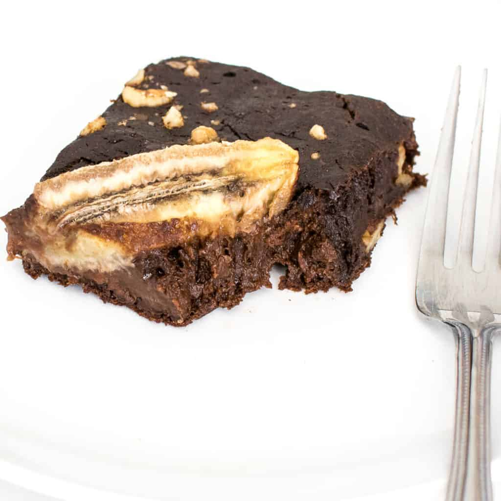 a 45 degree angle view of half eaten slice of banana brownies.