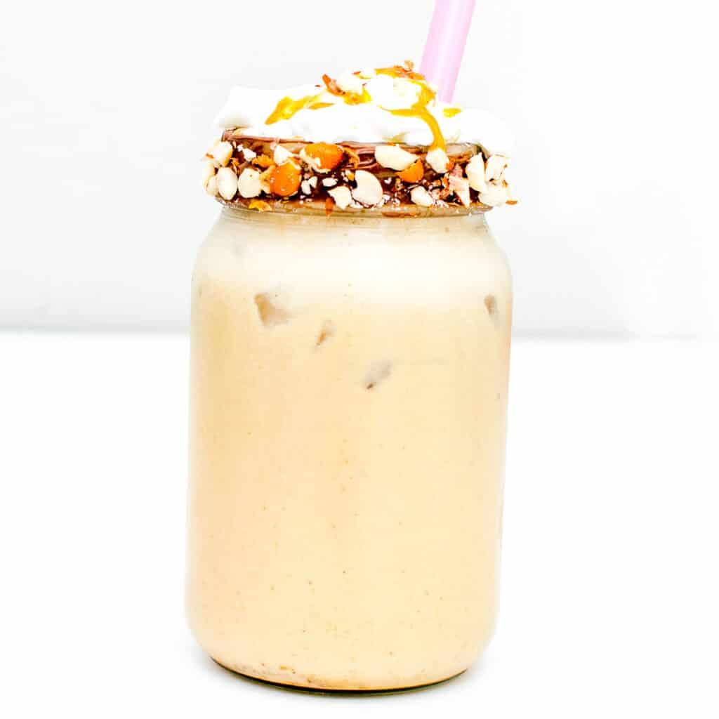 a tall glass jar with peanut butter milkshake.
