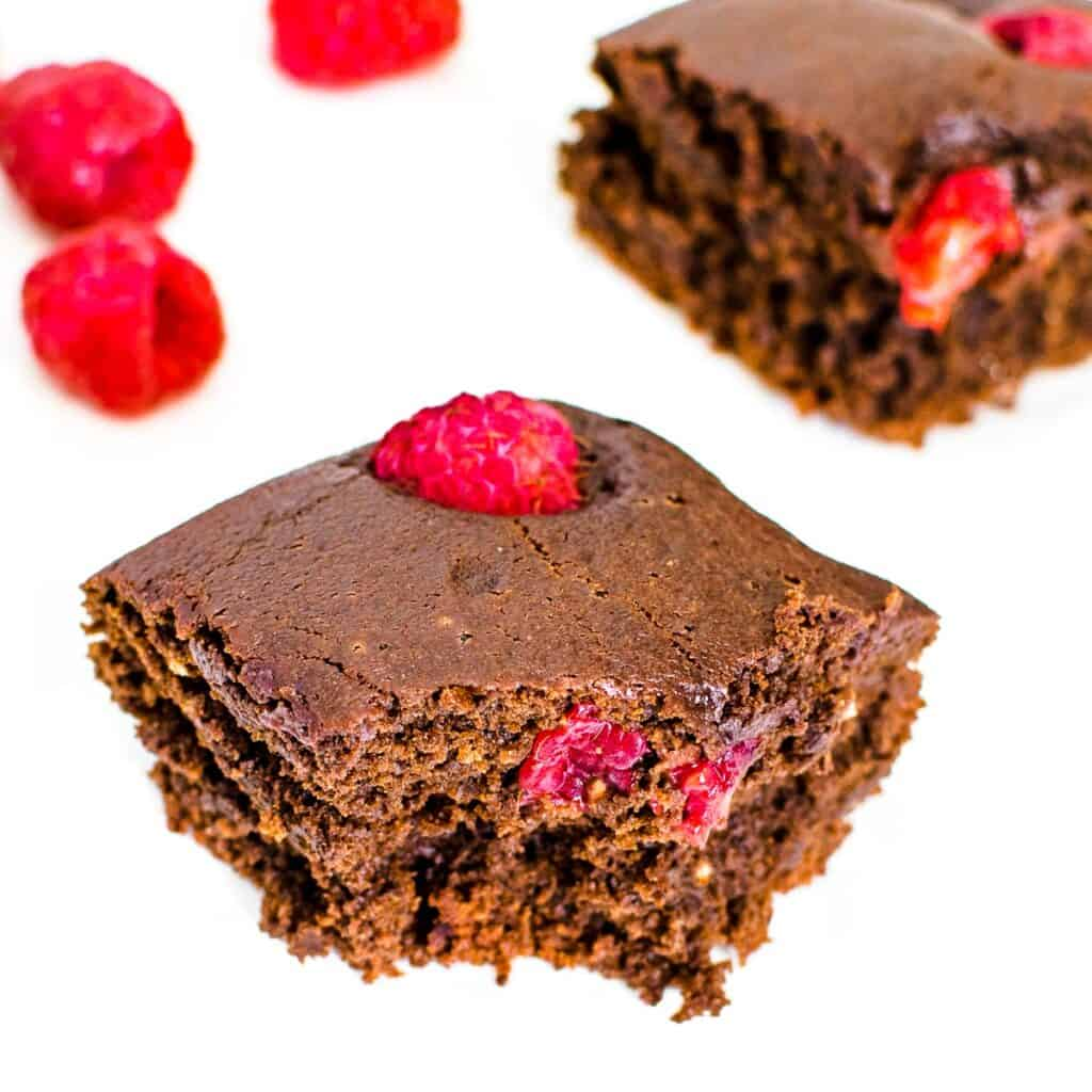 a 45 degree angle view of half eaten slice of raspberry brownies.