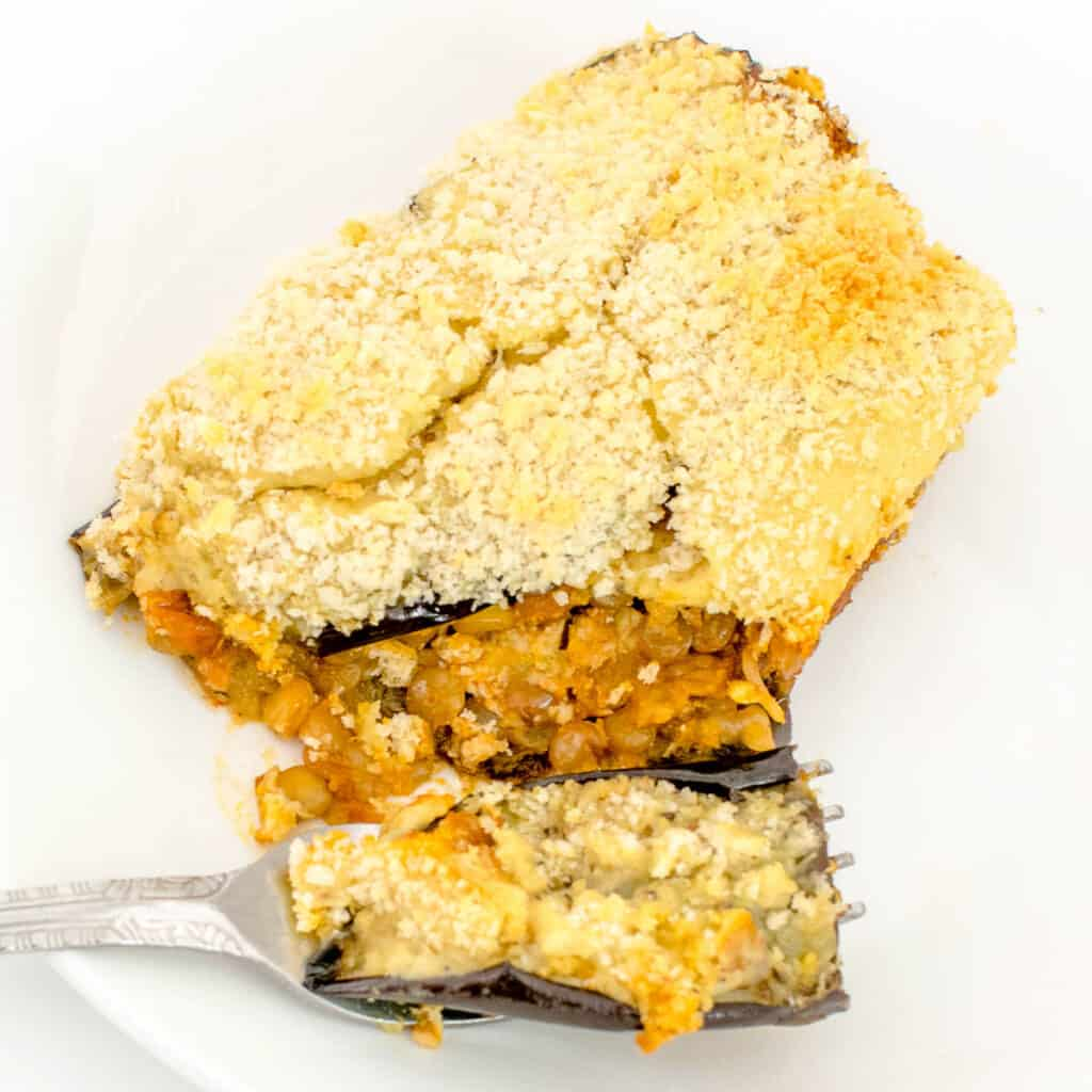 a 45 degree angle view of a fork holding a bite of vegan moussaka.