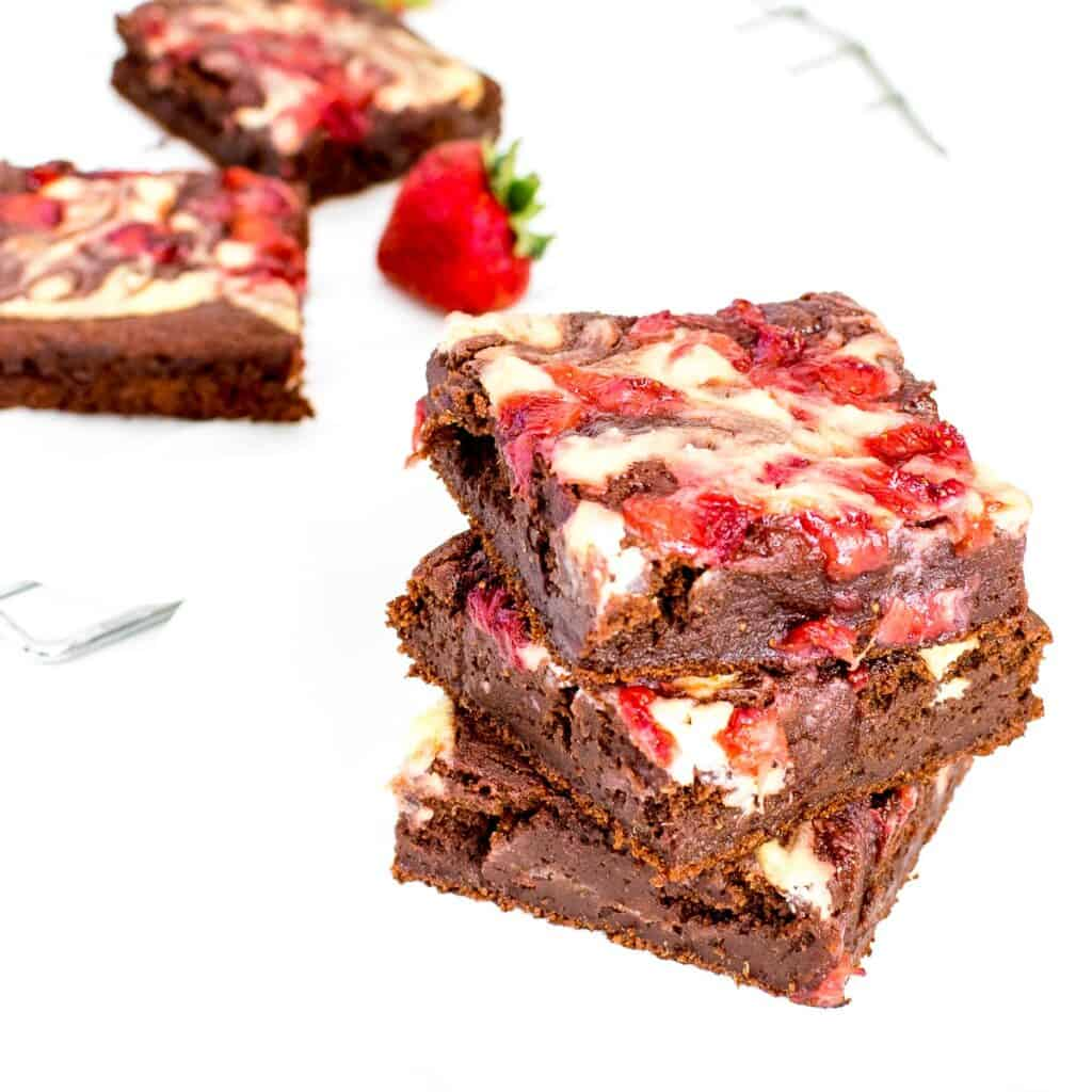 a 45 degree angle view of stacked strawberry cheesecake brownies.