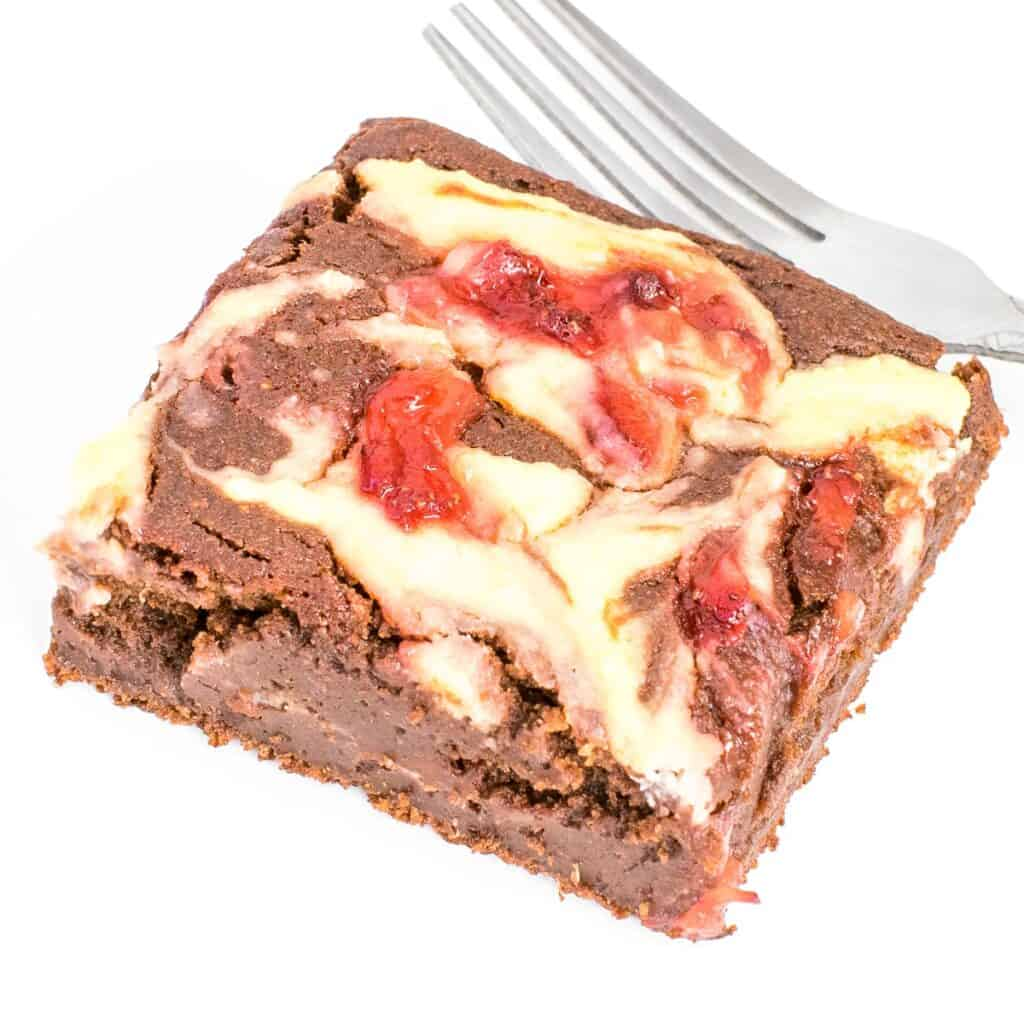 a close up view of a slice of strawberry cheesecake brownies.