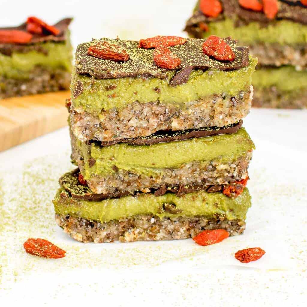 a front view of stacked matcha bars with more of them in the background.