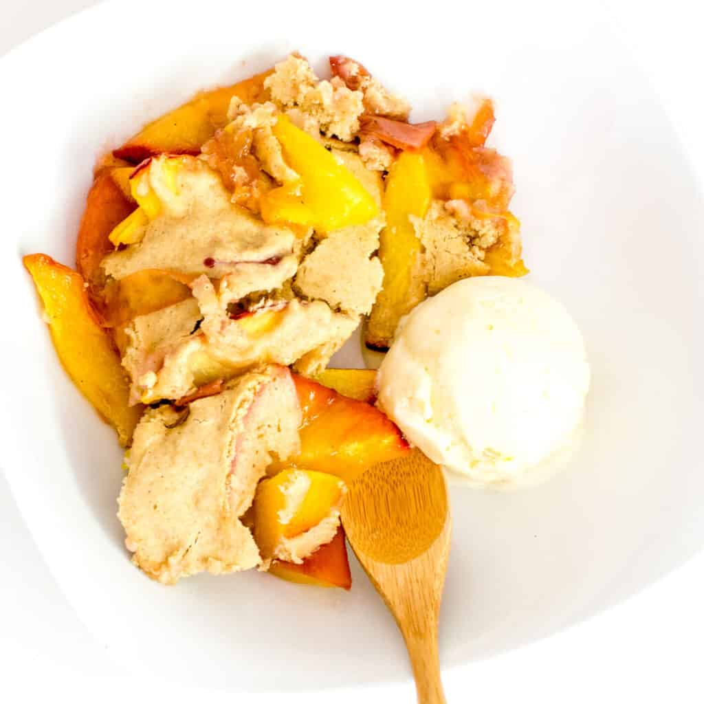 vegan peach cobbler in a bowl served with ice cream.