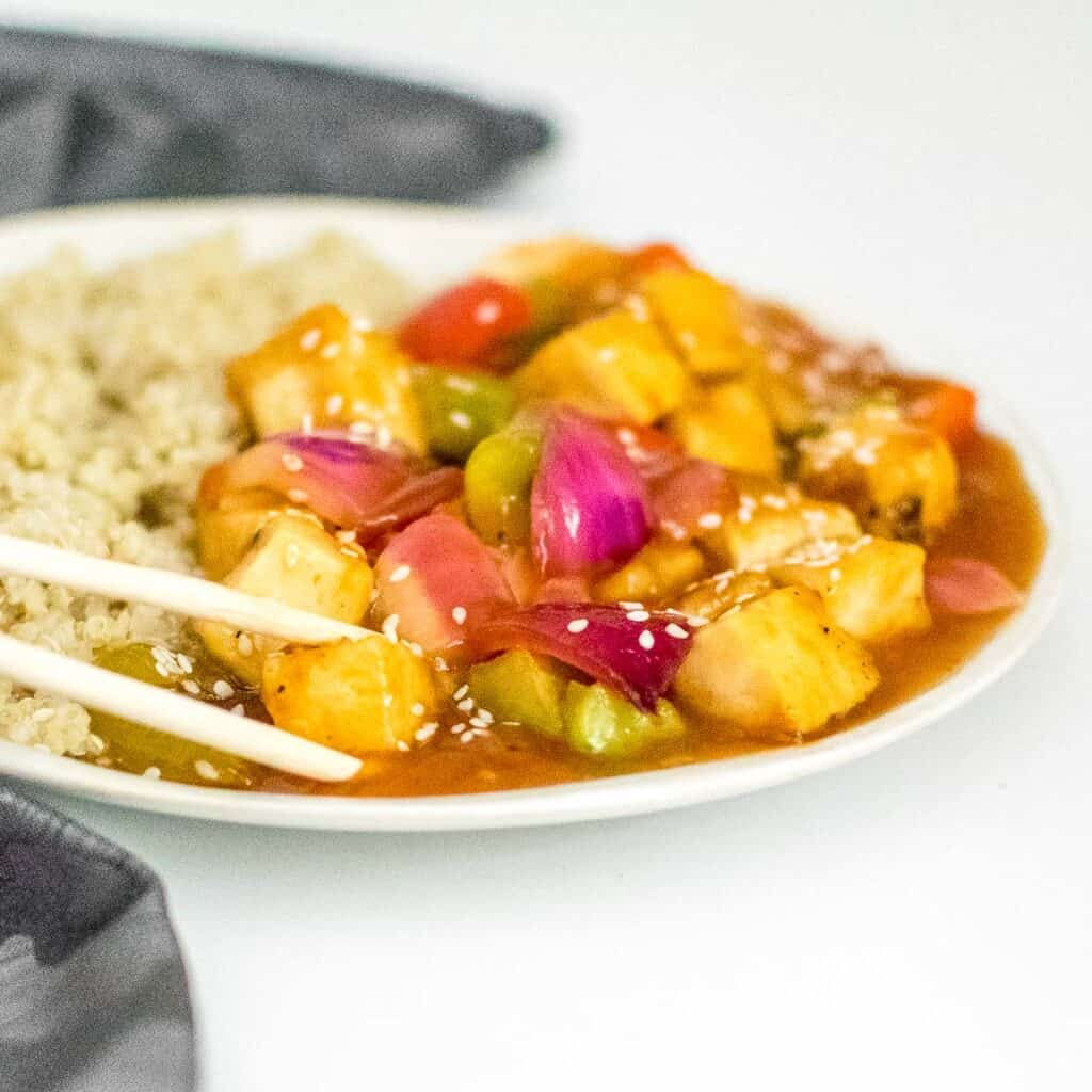 a chopstick picking up sweet and sour tofu.