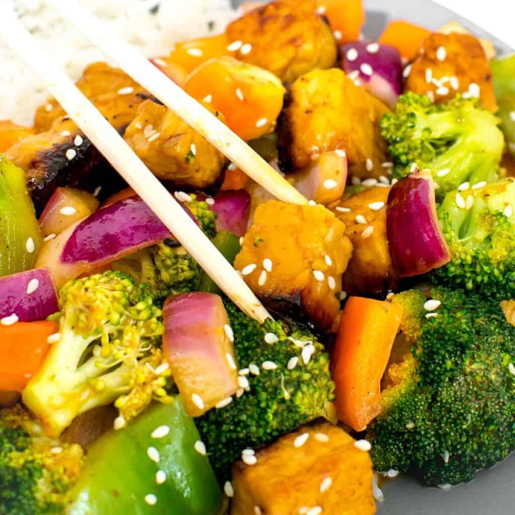 a close up view of chopsticks picking up tempeh stir fry