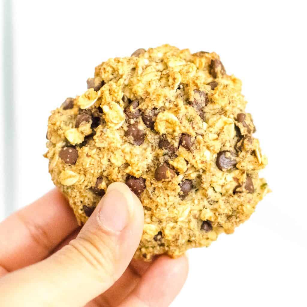 a hand holding vegan oatmeal chocolate chip cookies