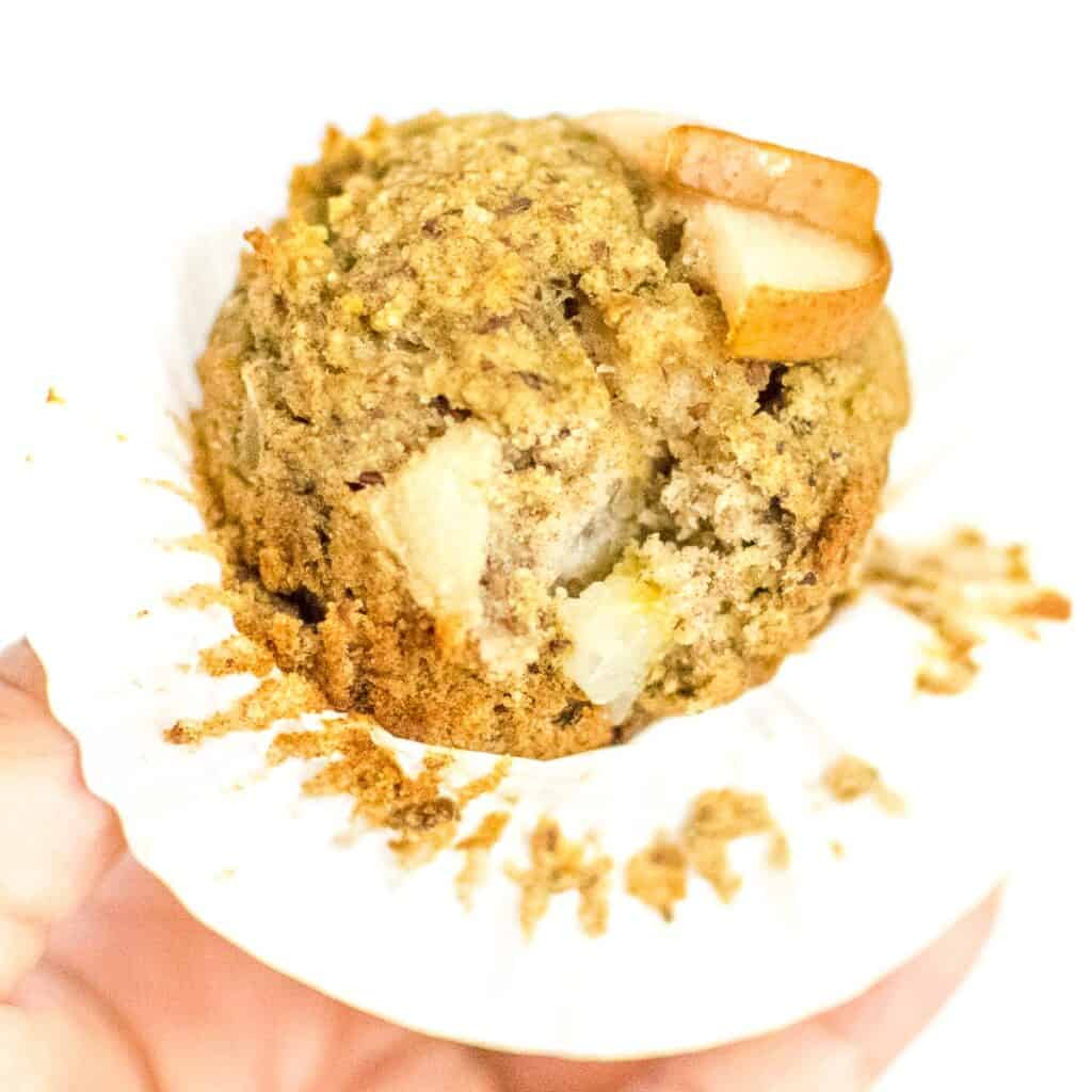 a hand holding pear muffin and showing the inside of it.