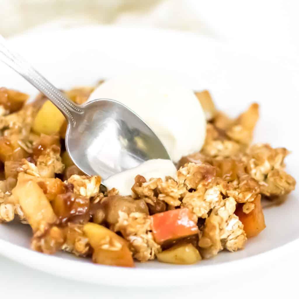 a spoon digging into vegan apple crisp.