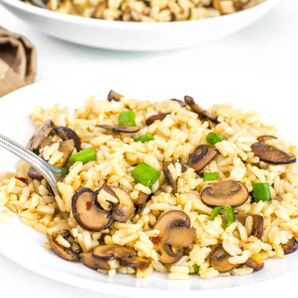 a fork digging into mushroom fried rice.