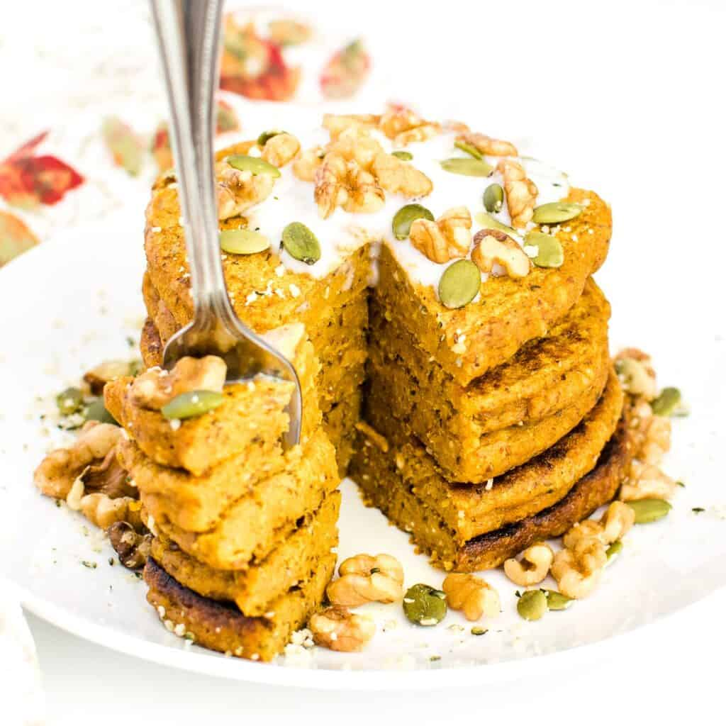 a fork dug into sliced stack of vegan pumpkin pancakes.