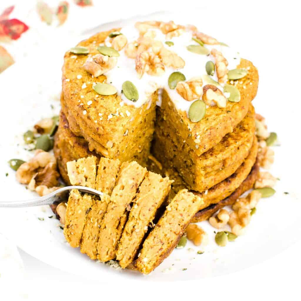 sliced pieces of vegan pumpkin pancakes with a fork.