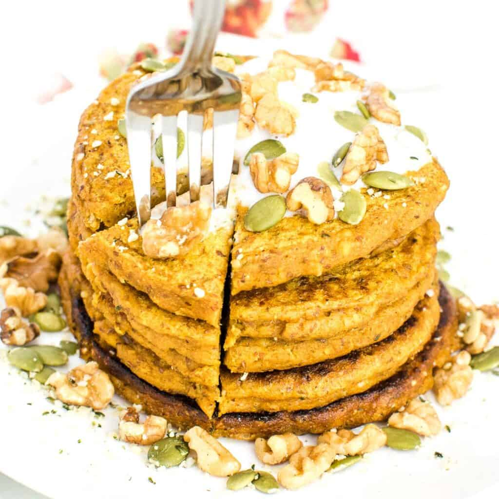 fork digging into the big stack of vegan pumpkin pancakes.