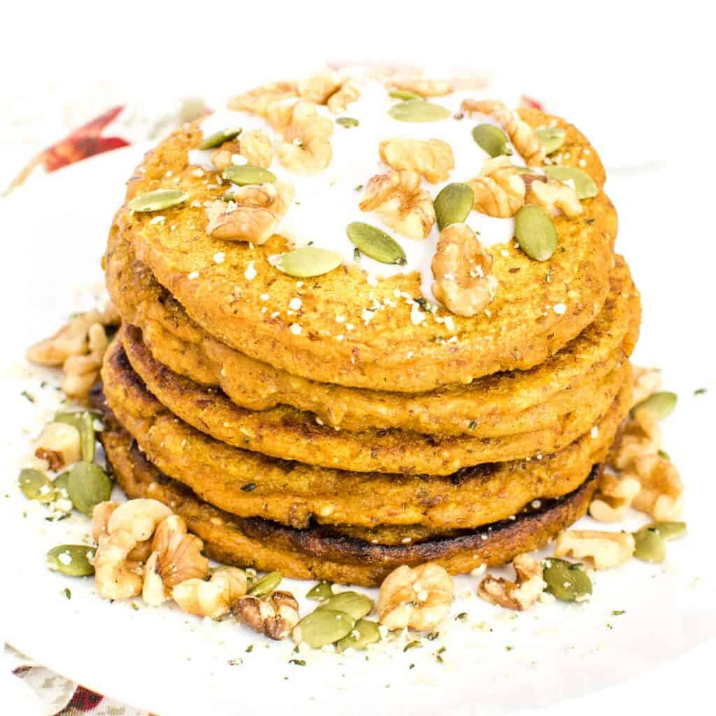 a 45 degree angle view of stacked vegan pumpkin pancakes.