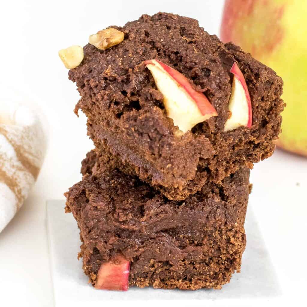 a close up view of stacked vegan applesauce brownies.
