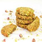 stacked pistachio cookies with half broken cookies around the stack.