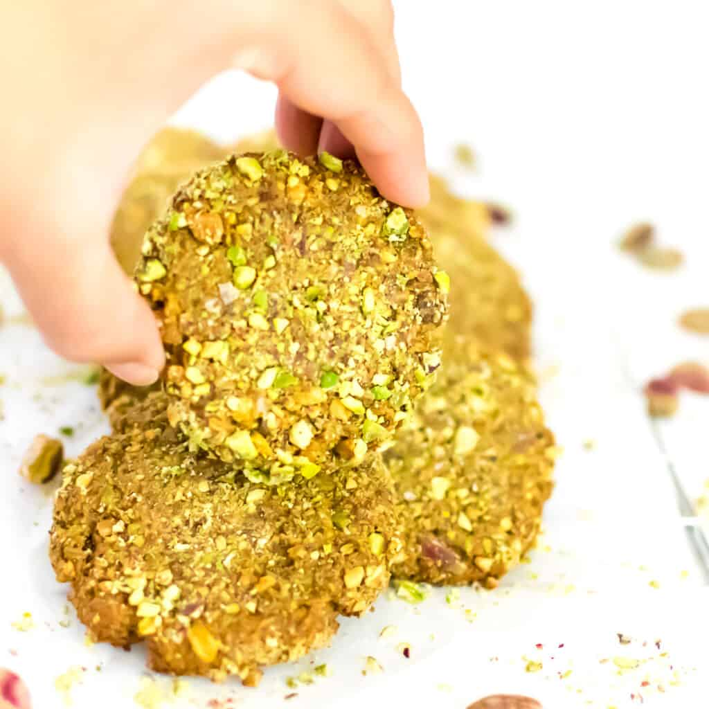 a hand picking up a pistachio cookie.